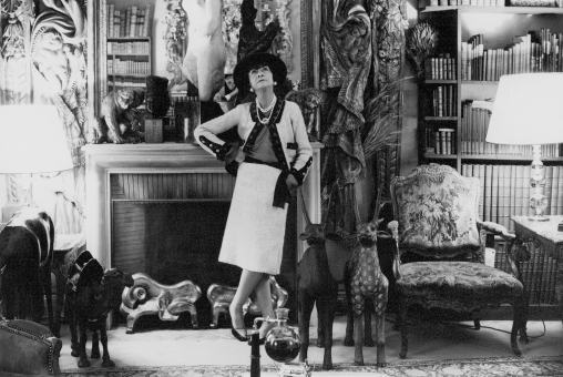Coco Chanel wearing her classic 'Chanel Suit' photographed in her apartment on Rue Cambon.